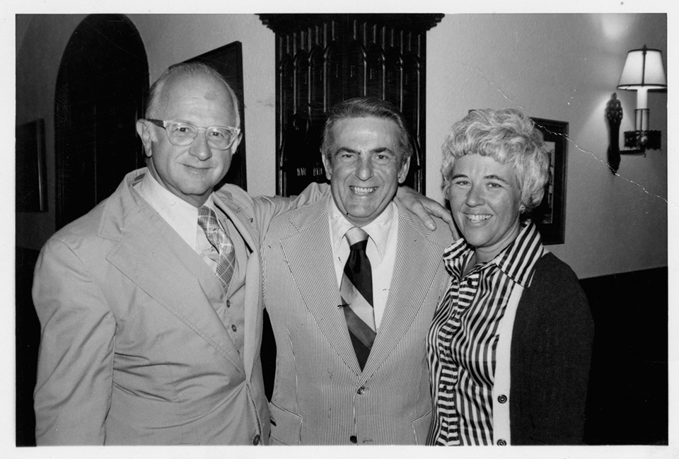 R.S. Mendelsohn standing with one arm around Abner Mikva, [former former U.S. Congress Representative]. To the other side of Mikva is Rita Mendelsohn.