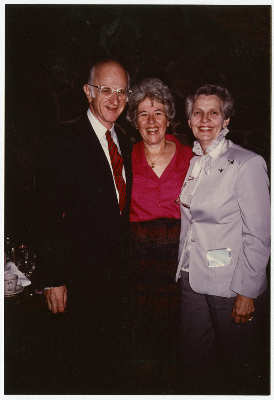 R.S. Mendelsohn standing with Rita Mendelsohn and Rosalie Tarpening, a midwife on whose behalf he testified in in court, in some sort of a dining hall.