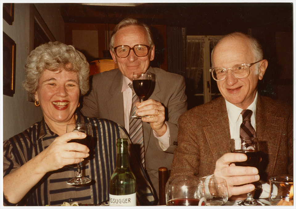 R.S. and Rita Mendelsohn sitting at a table in Zürich, Switzerland holding wineglasses, with Fred Pestalozzi (Head of Biostrath) behind them.