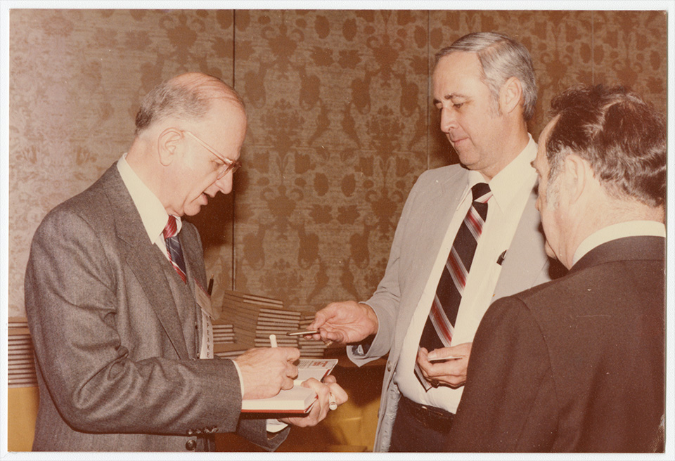 R.S. Mendelsohn standing in front of a table with a stack of books on it, signing one of the books as two men (one of whom is Harrison Coulter, M.D., a homeopathic doctor) look on and one appears to be handing him something square and metallic.