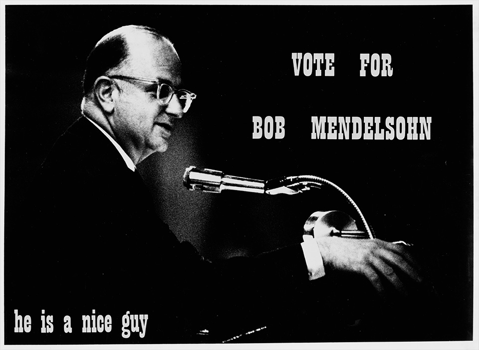 "Profile shot of R.S. Mendelsohn in a suit and standing behind a podium with a microphone, with ""VOTE FOR BOB MENDELSOHN he is a nice guy"" printed on it"