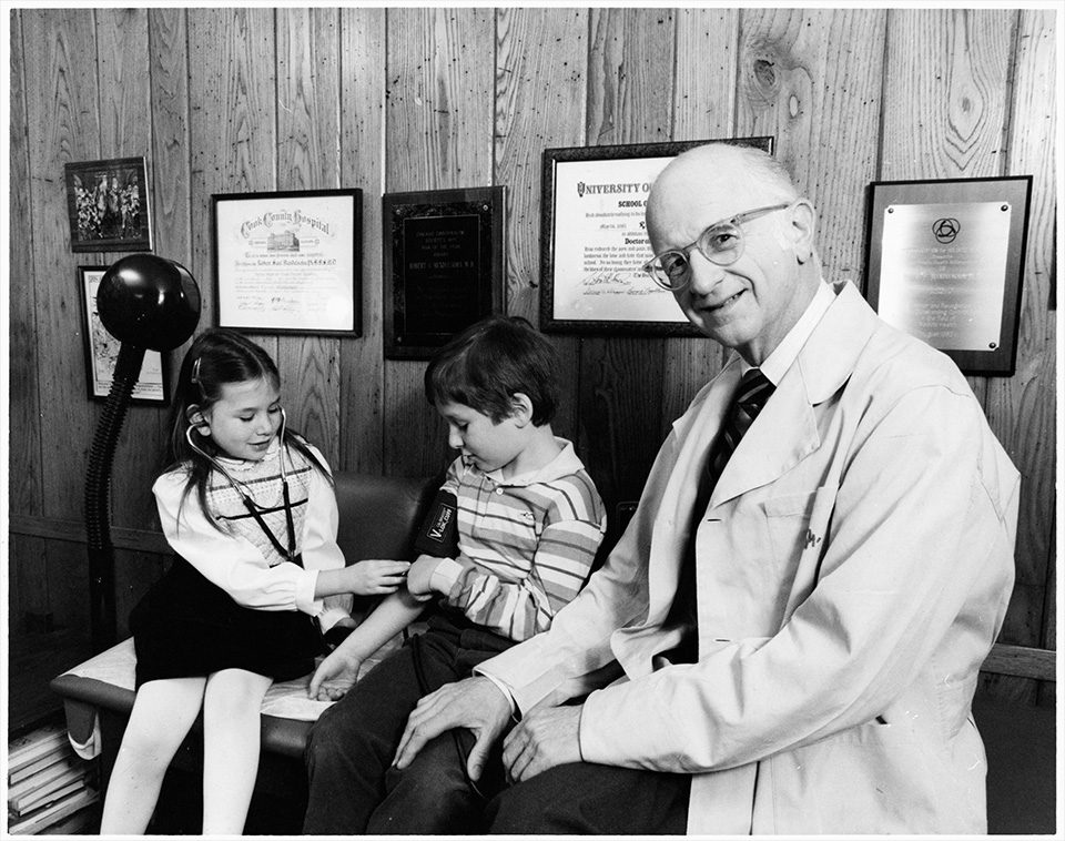 R.S. Mendelsohn wearing a laboratory coat in a doctor's office, with painting prints and awards/certificates hanging on the wall. He is sitting on a seat or examination table with his hand on the knee of a little boy to his right. To the right of the little boy (who is wearing a blood pressure cuff) is a little girl examining his arm with a stethoscope.