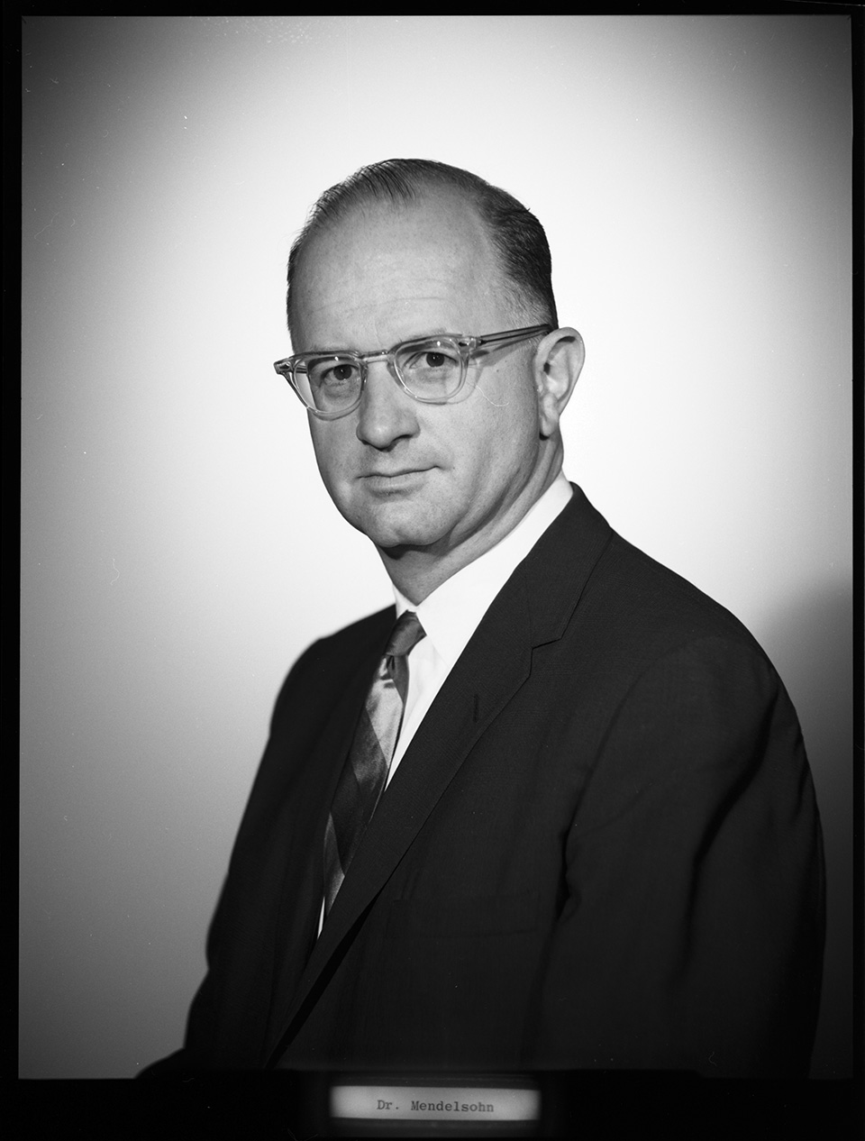 Close-up/headshot of R.S. Mendelsohn in a suit, with his body turned slightly to the side and looking directly at the camera