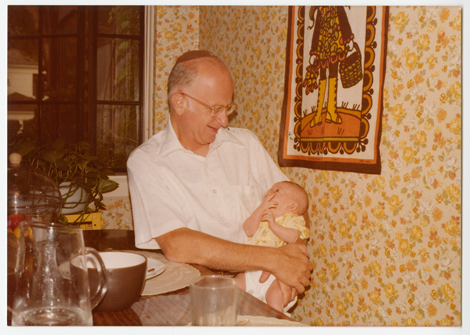 R.S. Mendelsohn sitting at a table laid out with dishes [in a dining room?] and wearing a yarmulke, holding baby Channa Lockshin.