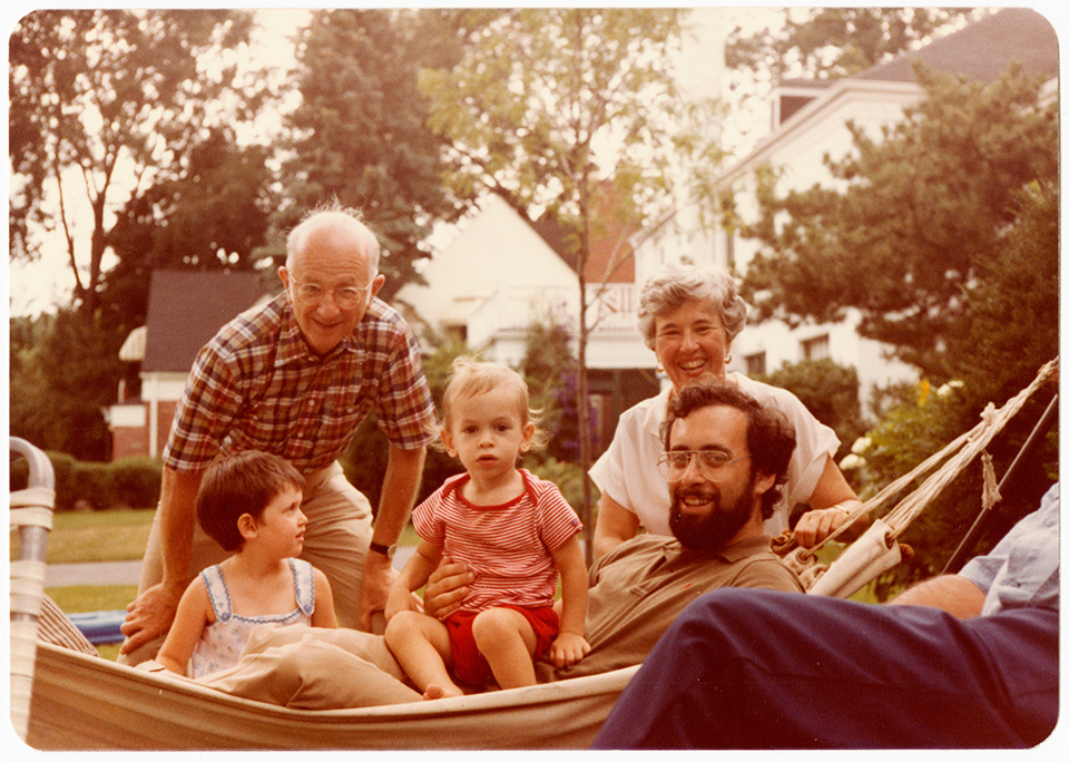 R.S. and Rita Mendelsohn, standing in a yard behind a hammock containing Channa Lockshin and Jonah and David Lowenfeld.