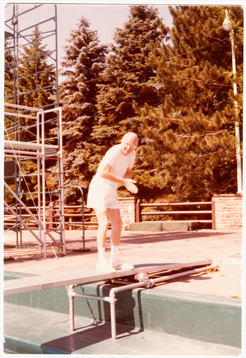 R.S. Mendelsohn standing to the side of a diving board, posing as if he is going to dive despite having socks and sneakers on.