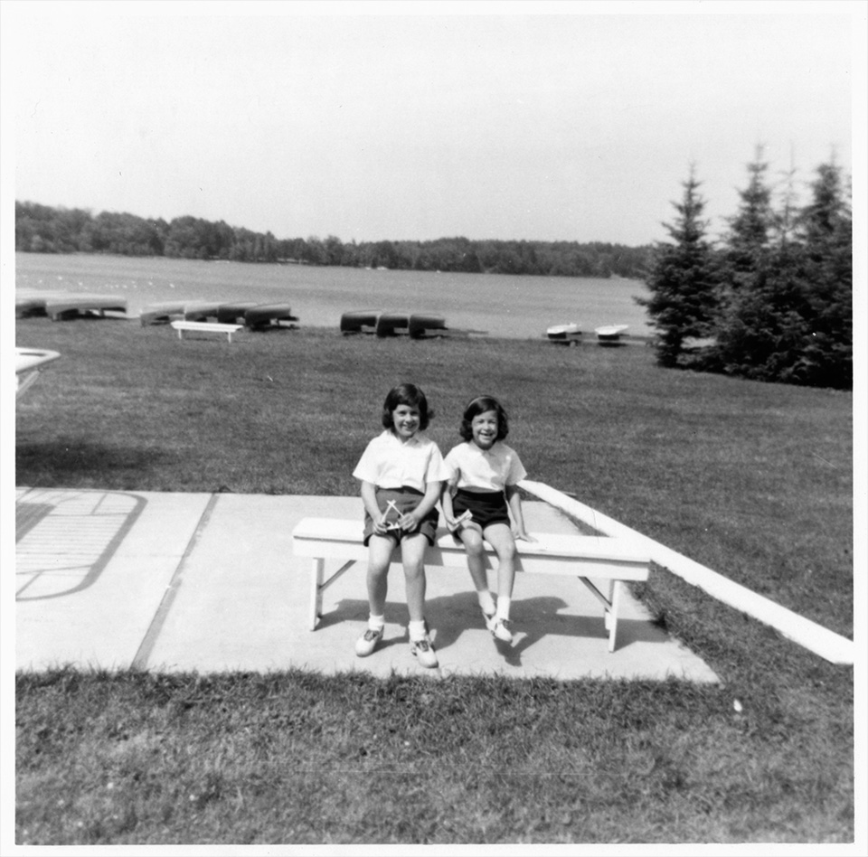 Ruth and Sally Mendelsohn sitting on a bench in front of a body of water with kayaks on its shore, at Camp Marimeta in Eagle River, Wisconsin (where R.S. Mendelsohn was doctor from 1956-1967).