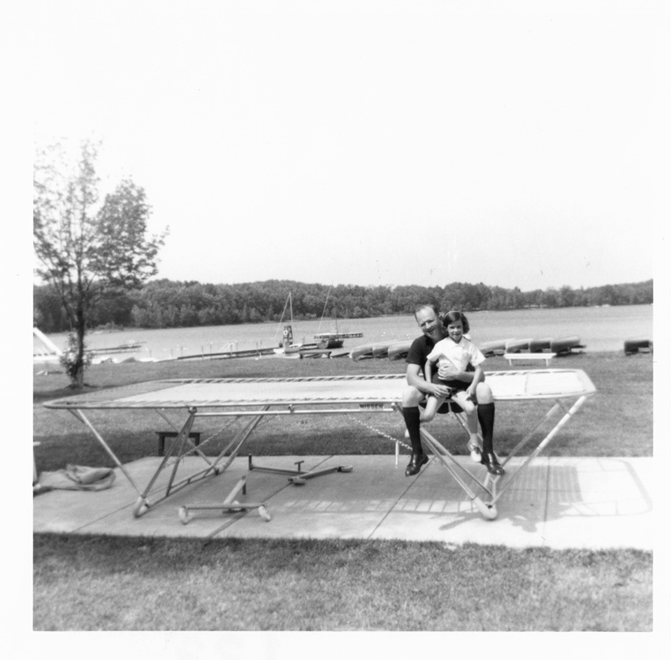 R.S. and Sally Mendelsohn sitting [on a trampoline?] in front of a body of water with kayaks on its shore, at Camp Marimeta in Eagle River, Wisconsin (where R.S. Mendelsohn was doctor from 1956-1967).
