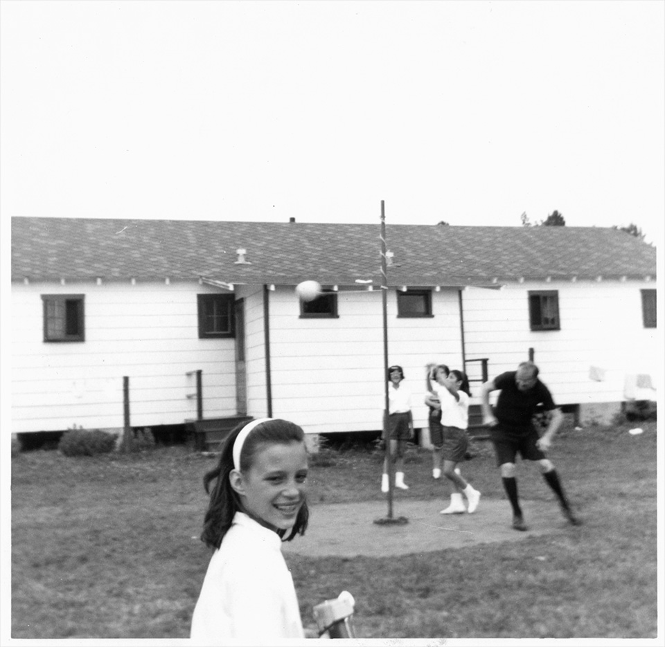 Unidentified girl stands in foreground, as R.S. Mendelsohn ducks while he and 3 girls play tetherball, at Camp Marimeta in Eagle River, Wisconsin (where R.S. Mendelsohn was doctor from 1956-1967).