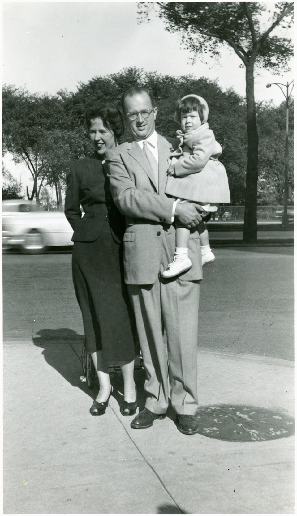 R.S. holding Ruth Mendelsohn, as he and Rita stand on a sidewalk in front of some trees.