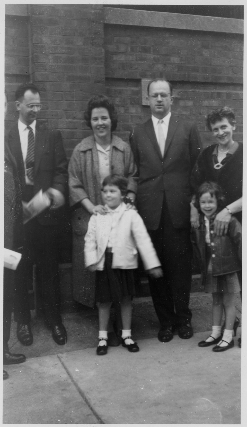 Unidentified man who is partially cut off; Marc, Rita, R.S., and Rosamond Mendelsohn stand in front of a brick-walled building. Rita has her hands in front of her on Ruth's shoulders, as does Rosamond on Sally's shoulders. Rosamond, Sally, Rita, and Ruth are smiling.