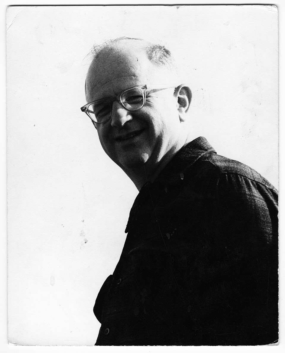 Close-up/headshot of R.S. Mendelsohn with his body facing to his right, while he is looking down and slightly past the camera. He is smiling.