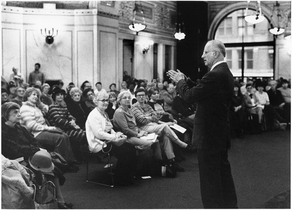 R.S. Mendelsohn in a suit, speaking to a seated audience [at the Preston Bradley Hall of the Chicago Public Library's Cultural Center] while holding his hands together in front of him.