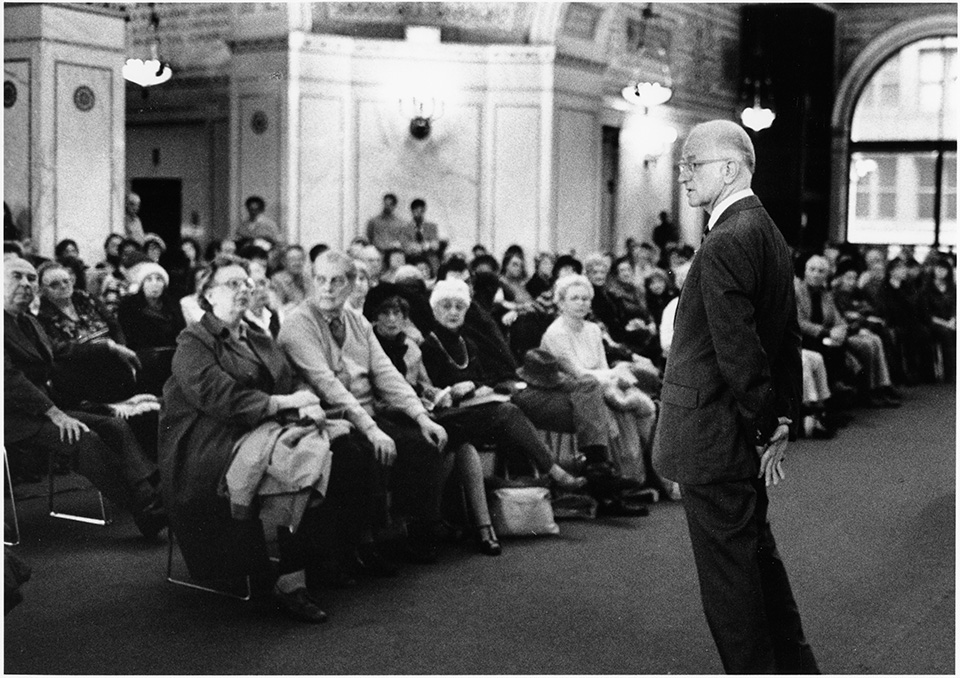 R.S. Mendelsohn in a suit, speaking to a seated audience [at the Preston Bradley Hall of the Chicago Public Library's Cultural Center], clasping his hands behind his back and leaning forward.