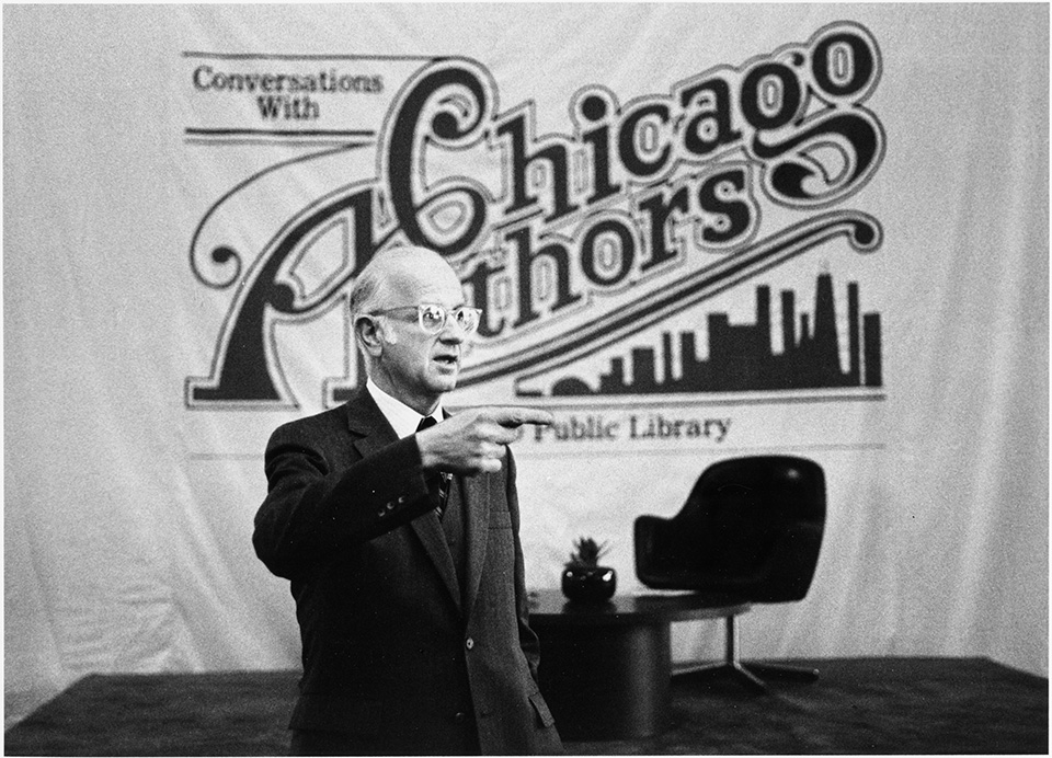"R.S. Mendelsohn dressed in a suit, looking to his left side and pointing, while standing in front of a banner. The banner reads ""Conversations with Chicago Authors, [Chicago] Public Library."""
