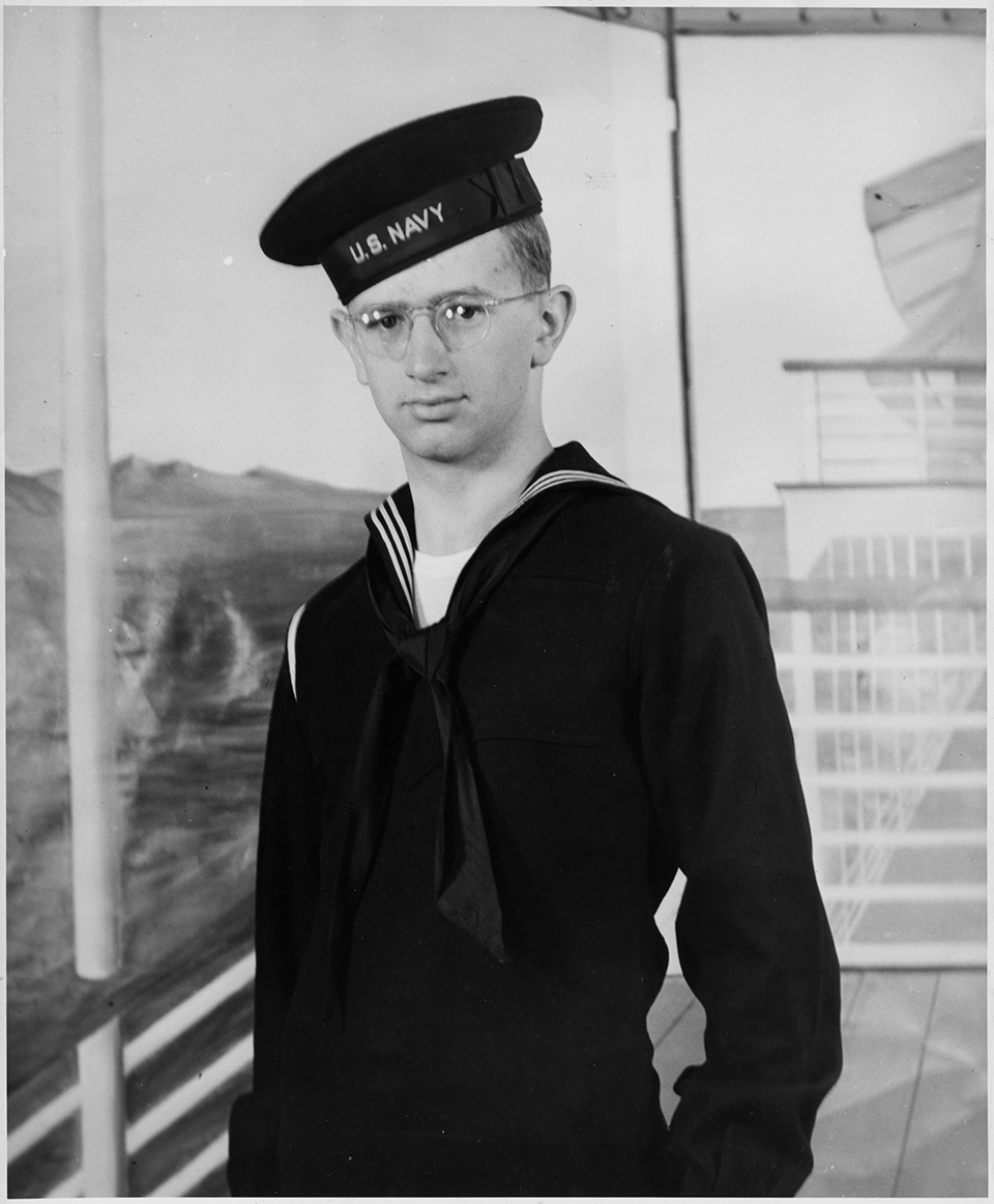 R.S. Mendelsohn as a young man, in a U.S. Navy uniform. A photographic backdrop resembling the deck of a ship at sea is visible behind him.