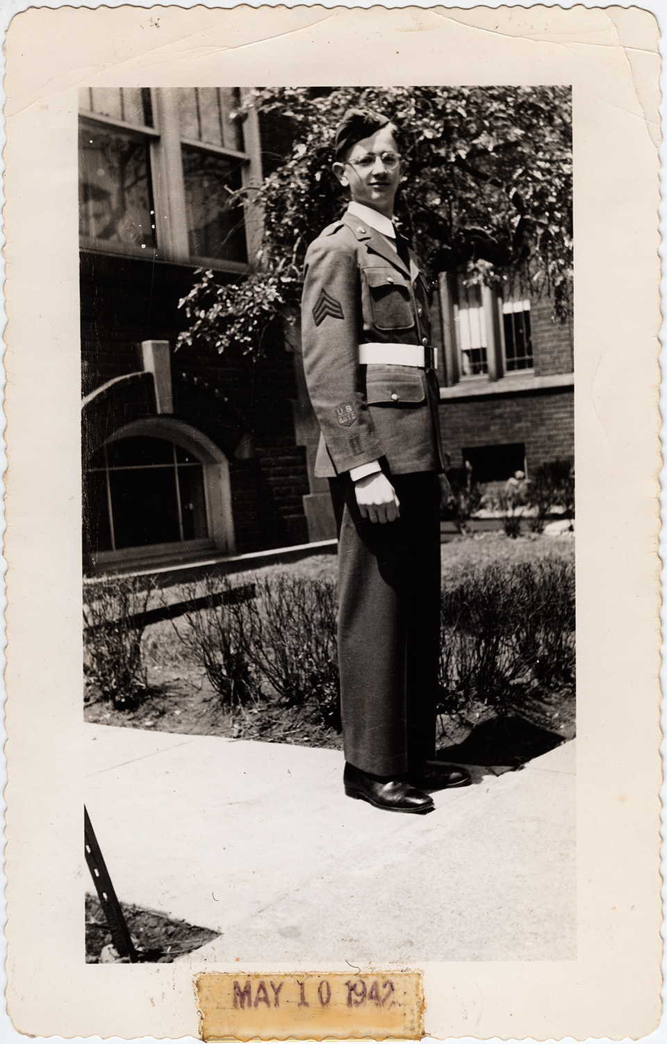 "R.S. Mendelsohn as a young man, in a Reserve Officers' Training Corps (ROTC) uniform and standing on the sidewalk in front of a building. A patch labelled ""US 4010"" is visible on his right sleeve. Part of a tree and lawn are visible behind him."