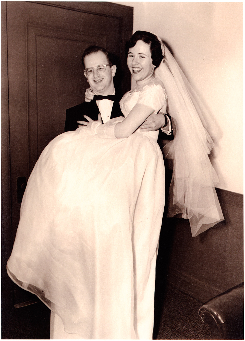 Image of R.S. and Rita Mendelsohn on their wedding day, dressed in their groom's and bride's outfits. R.S is carrying Rita as they stand in front of a door. A portion of a couch is also visible.