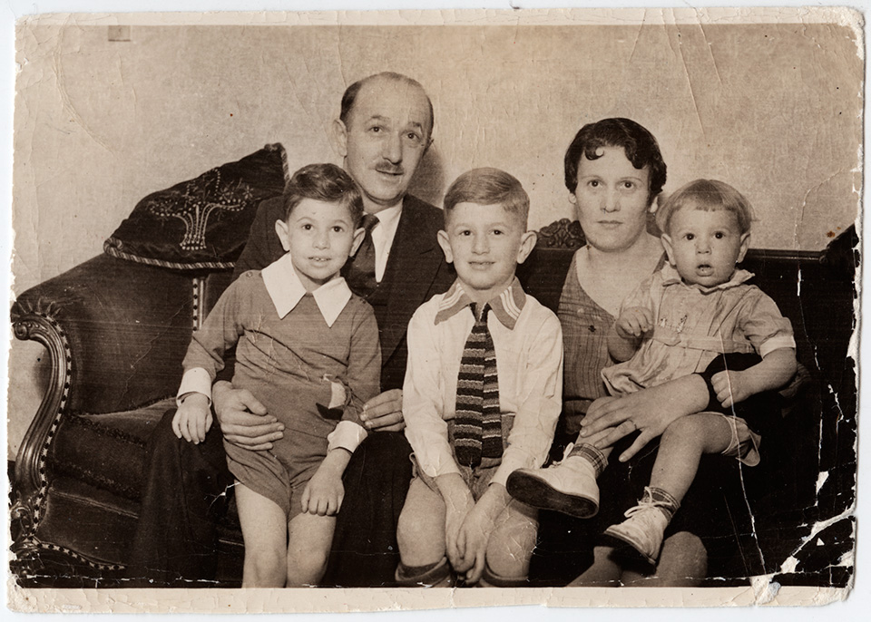 R.S. Mendelsohn as a child, sitting on a couch with his parents and younger brothers Mark and Allan. He sits between his parents, while they each hold one of his younger brothers on their laps.