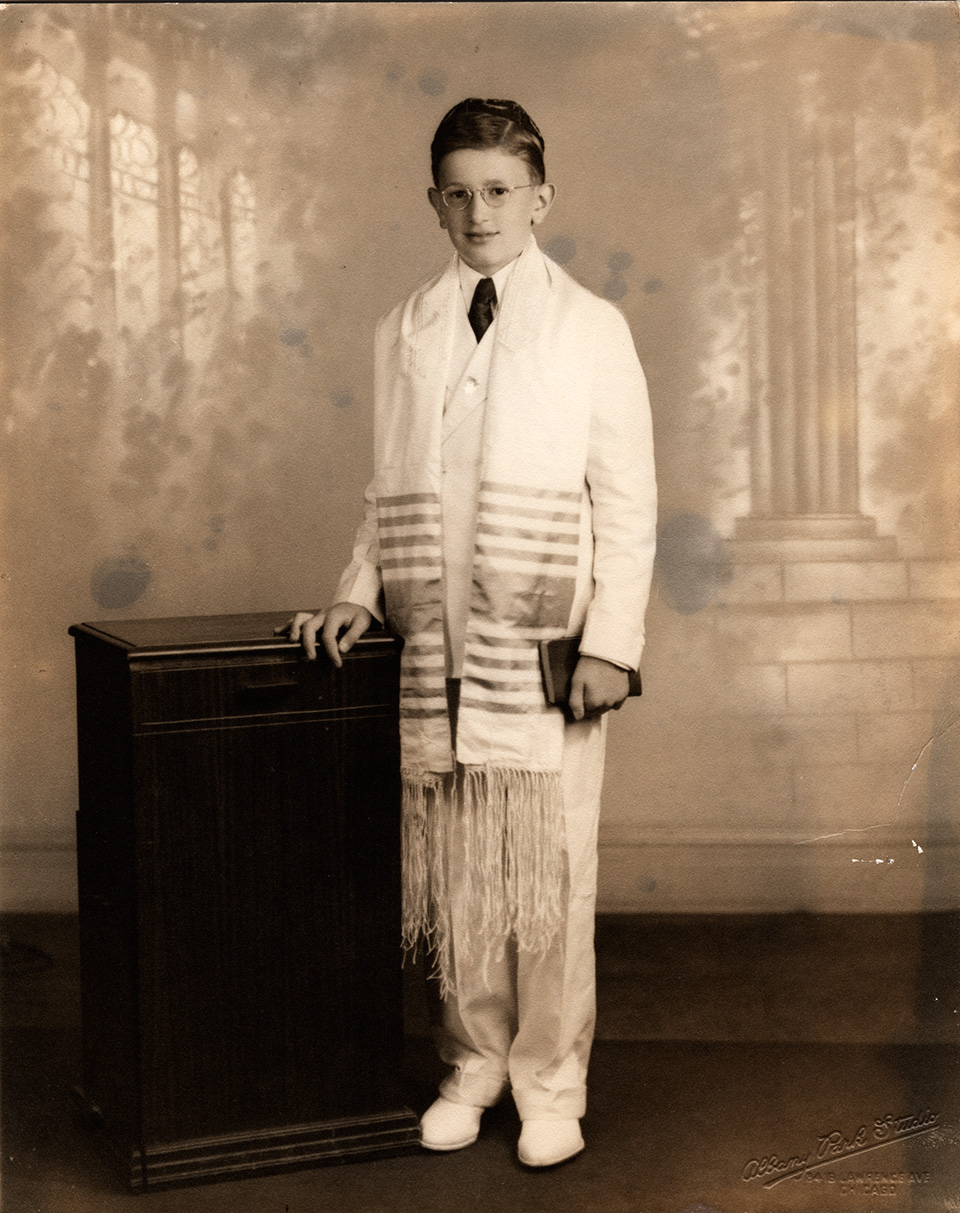 R.S. Mendelsohn as a young man, wearing a white suit with tie, yarmulke, and tallit. He is holding a book in his left hand, while resting the other hand on a [podium]. A photographic backdrop with a wall and column, windows, and foliage painted on it is visible behind him.